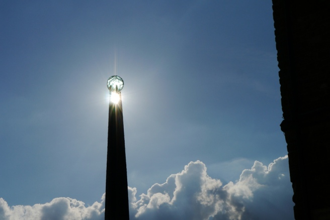 Sun at peak of tower.