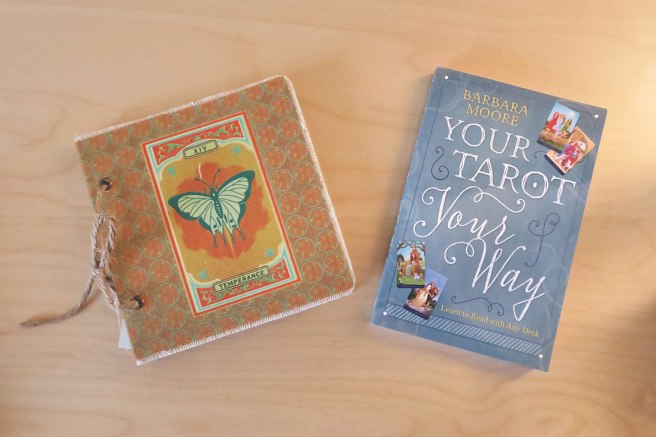 A blank book with the tarot card Temperance on the front cover, and the book Your Tarot Your Way.