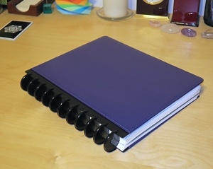 A purple discbound notebook lying on a table.